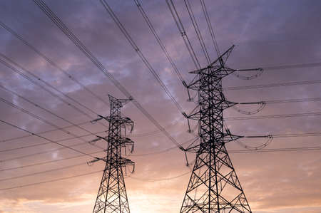 silhouette of high voltage electric poles and lines, High voltage electric transmission tower at sunset sky background.