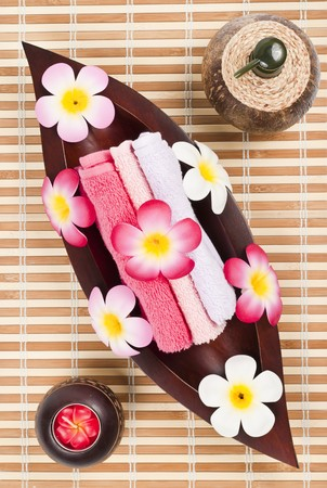Fresh towels in the wooden leaf tray on the bamboo mat photo