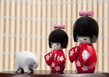 Small Japanese dolls and small ceramic elephant Stock Photo