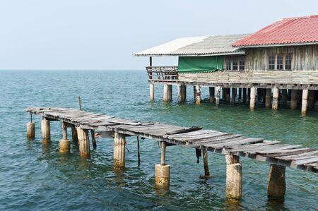 Antiguo puente en el mar cerca de la antigua casa de roto