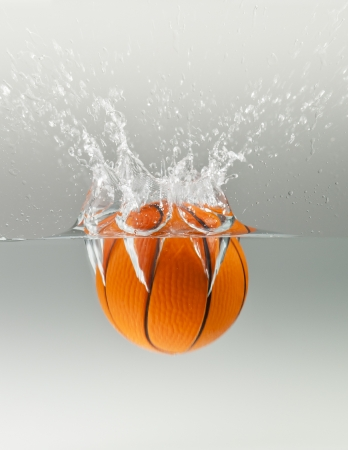 Falling basketball into water isolated on grey background