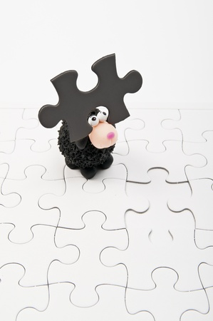 Black sheep with one dark gray jigsaw on head Stock Photo