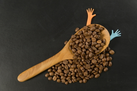 Coffee bean in wooden spoon with two colorful hands Stock Photo - 19492498