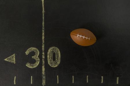 Football on the black field near 30 yards line Stock Photo - 19835405