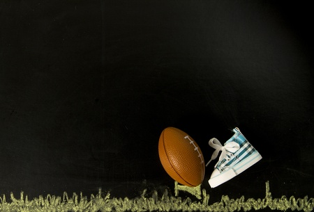 Football on tee with one shoe in black background Stock Photo - 19835404