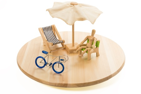 Wooden human model in relax time with blue bicycle in tray Stock Photo - 20761582