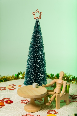 Model sit on green chair with Christmas tree isolated on soft green background Stock Photo - 21068618