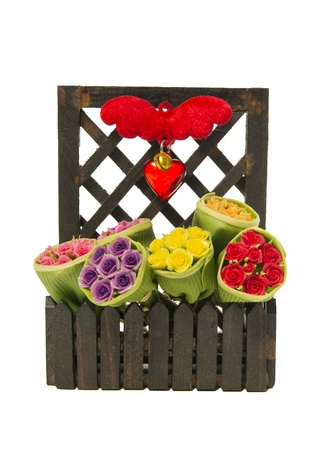 Bush of different color of roses and herart symbol in the wooden fence Stock Photo - 21493060