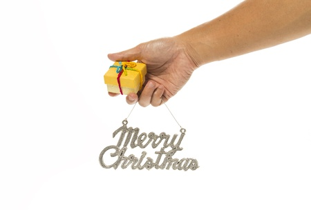 One hand holding yellow gift box and Merry Christmas sign