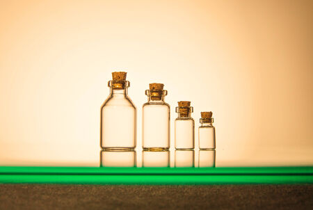 Four size of glass bottles isolated on yellow background photo