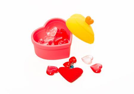 corazon cristal: Forma de coraz�n de cristal rojo y rosado en la caja aislada en el fondo blanco