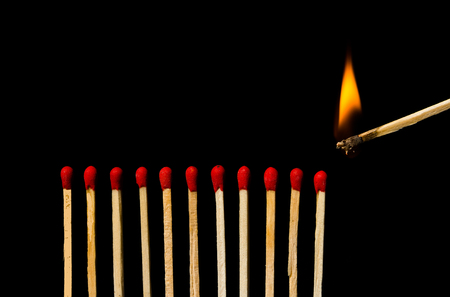 Burning match with row of matches isolated on black background Stock Photo