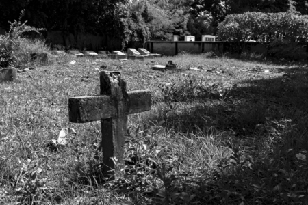 Old cross in graveyard with black and white
