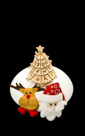 Reindeer and Santa face near wooden Christmas tree