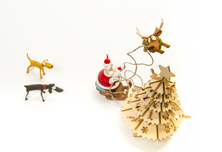 Reindeer pull up Santa sleigh into sky near Christmas tree Stock Photo
