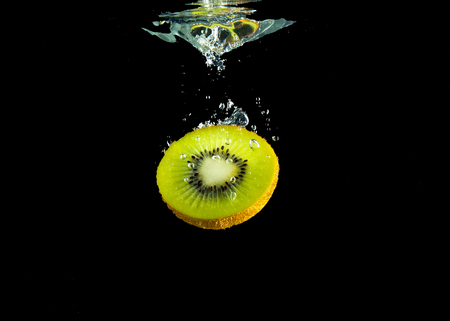 Piece of sliced kiwifruit in the watre isolated from black background