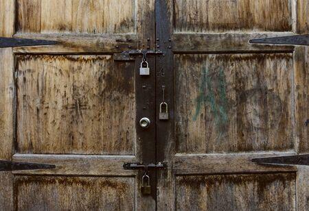 old wooden door with two lock of keys