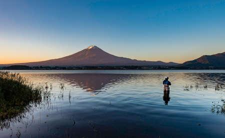 One man fishing in lake kawaguchi with Fuji Mountain background