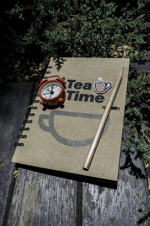 Tea time book with red alarm clock