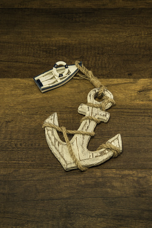 ship anchor: Small white ship with old large anchor on wooden background