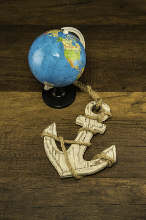 Globe model with old white anchor on wooden background Stock Photo