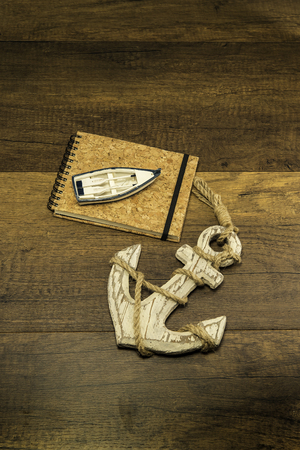 Cork cover book with small ship and large old white anchor Stock Photo