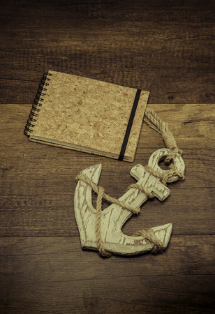 Old anchor with cork cover book on wooden background