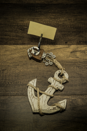 Old white anchor with wooden squid shape clip and blank piece of paper