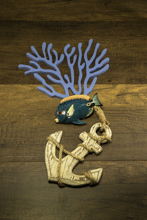 Anchor with fish and seaweed on wooden background