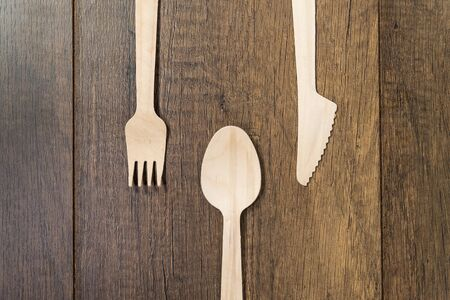 Set of wooden spoon fork knife on wooden background
