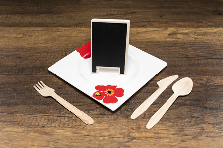 Small blackboard in white plate with spoon, fork and knife on wooden background