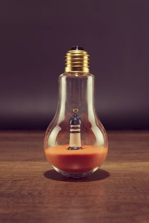 Lighthouse on orange sand in spiral bulb on wooden table