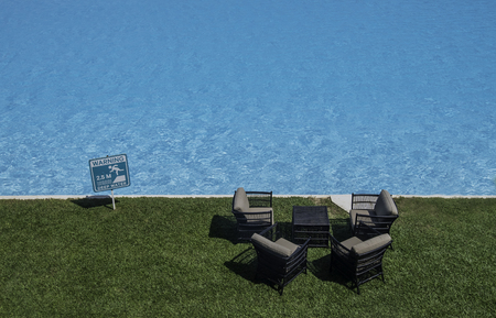Outdoor sofa near the pool with warning sign Stock Photo