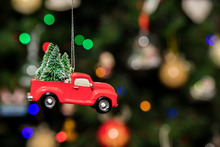 Red pickup car with Christmas tree hanging on Christmas tree