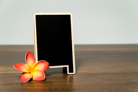 Blank wooden black board with yellow and orange plumeria flower
