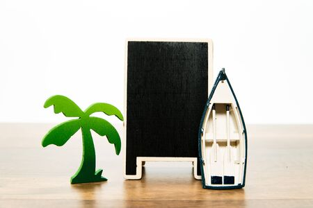 Blank wooden black board with green palm tree and white boat