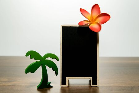 Blank wooden black board with Plumeria and Palm tree Stock Photo