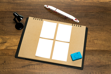 Small four blank white paper on brown paper with pen, lantern and blue camera