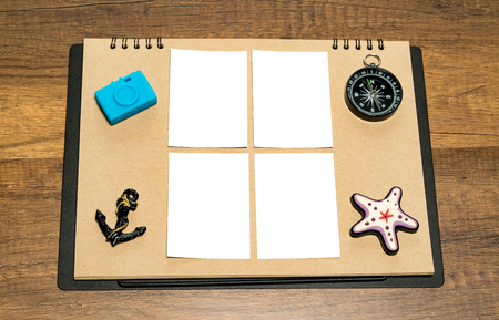 Small blank white sheet on brown paper with blue camera, anchor, compass and star fish magnet