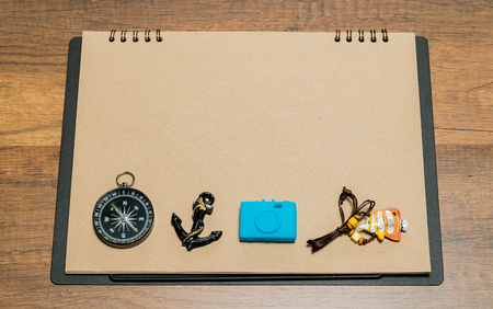 Blank brown paper with compass, anchor, blue camera and fish necklace on top