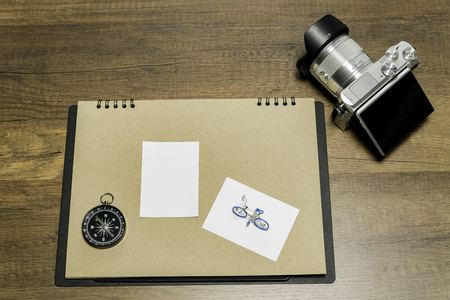 Blank small white paper on brown sheet with Camera and Compass