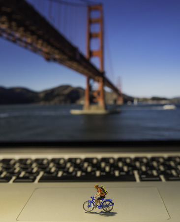 Man riding bicycle model on laptop with Golden Gate bridge background