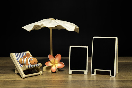 Blank black board with beach umbrella and bed with clown fish and flower