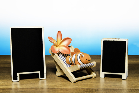 Clown fish on beach bed with flower and two blank back board Stock Photo