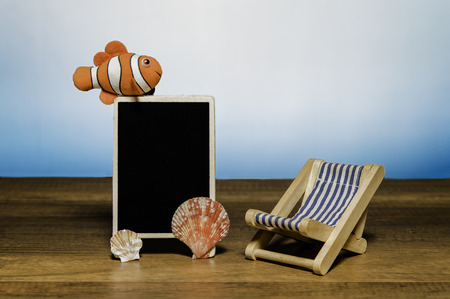 Blank black board with clown fish, sea shell and beach bed