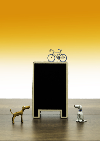 one bicycle model on top blank black board with two clay dogs
