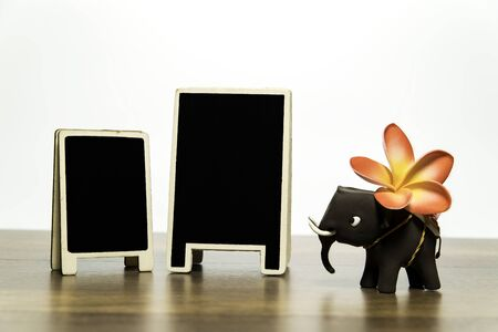 One clay elephant with plumeria flower and two blank black board
