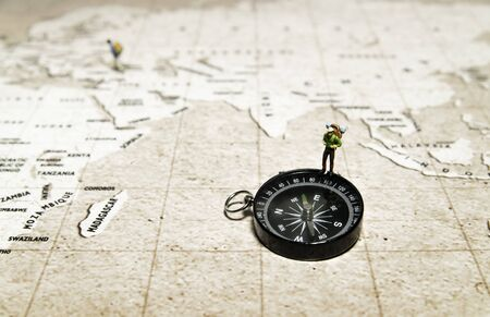 Tiny traveler model stand on compass over brown map