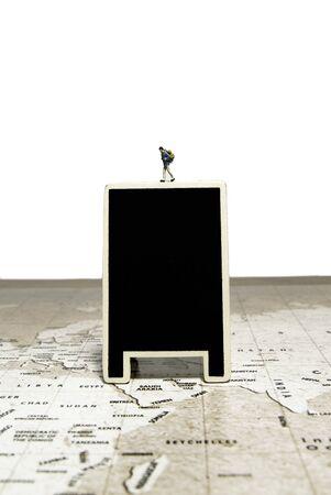 Walking tiny traveler model over blank black board on world map Stock Photo
