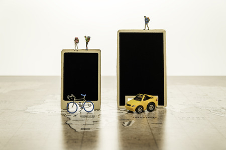 Two blank black boards with tiny human model with car and bicycle on world map